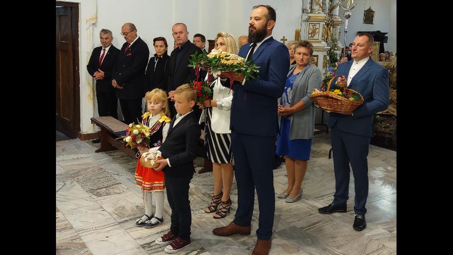 Starostowie dożynek przed ołtarzem w urzędowskim kościele wraz z przyniesionym chlebem dożynkowym.